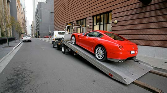 Ferrari on flatbed tow truck | Towing Companies Services | https://www.sfcitytowing.com