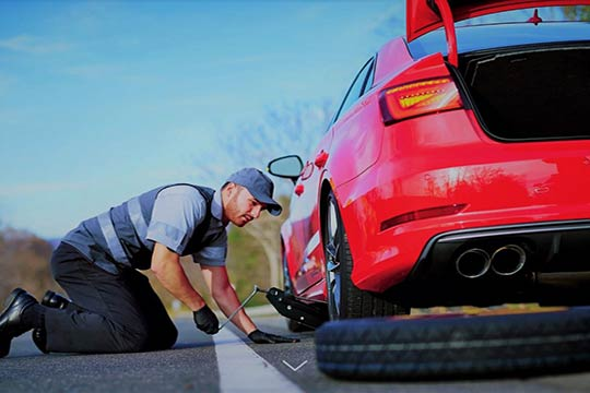 Tow operator changing a tire on a car on side of road | Emergency Roadside Assistance | https://www.sfcitytowing.com