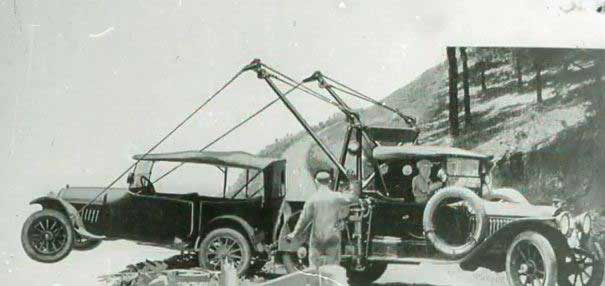 early 1900's tow truck lifting a vehicle | History of Towing | https://www.sfcitytowing.com