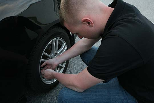Guy checking tire pressure with guage | Tire Maintenance Tips | https://www.sfcitytowing.com