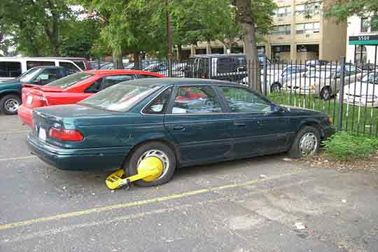 Car with a boot on the wheel | Towing enforcement booted vehicle | https://www.sfcitytowing.com