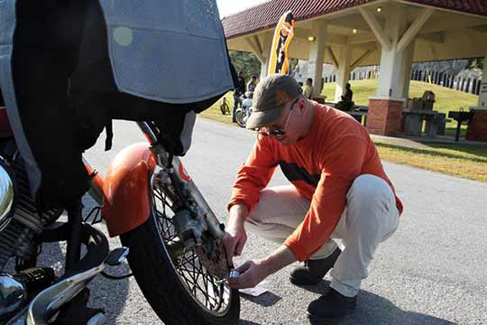 Man checking tire pressure on motorcycle | motorcycle safety tips | San Francisco Bay Area Towing