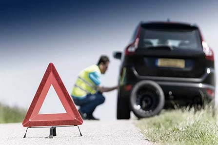 Changing tire roadside assistance on side of road